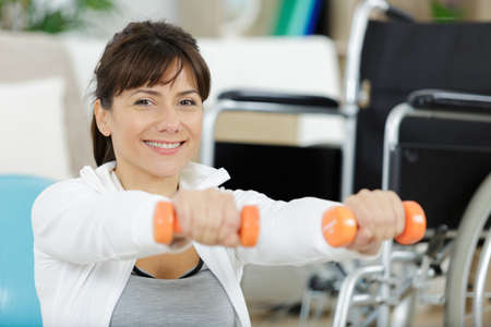 happy disabled woman doing exercises with dumbbells