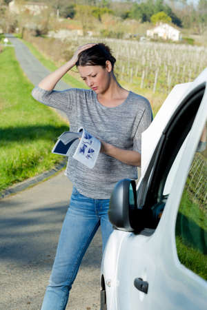 womn with broken down car reading instruction manual