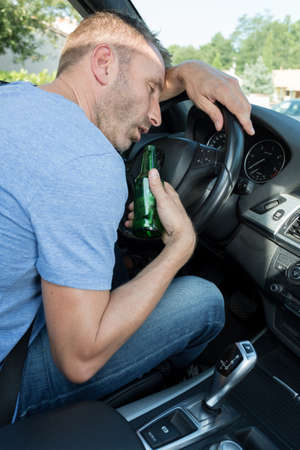 sleepy man drinking beer while driving a car