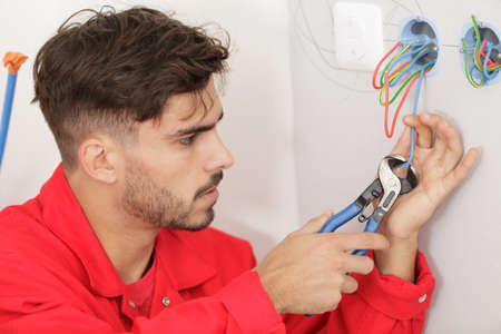 electrician trimming wire with cable cutters