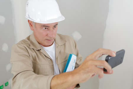 senior builder taking photograph with smartphone
