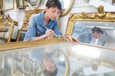 woman working on frame workshop Фото со стока