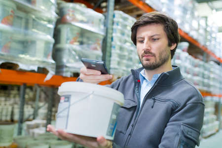 storeman scanning product in plastic container with smartphone