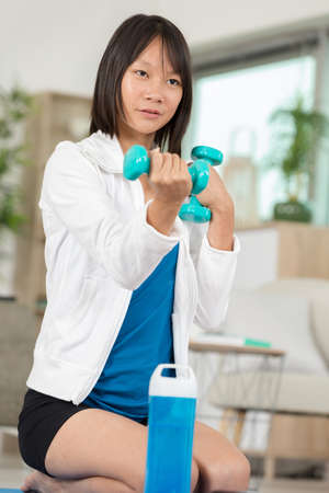 sporty pretty woman exercising at home with dumbbells