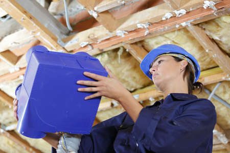 female builder during ventilation pipes installation