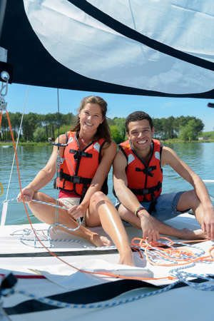 young couple wearing life jacket on board sailboat