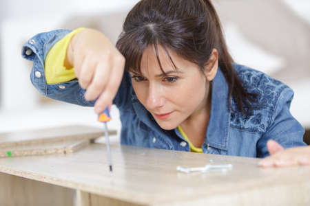 a woman during assembling furniture from chipboard