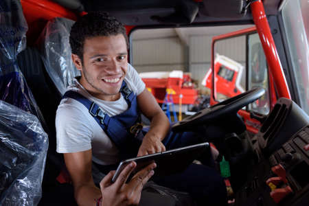 portrait of young mechanic in cab of truck with tablet