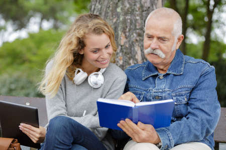 young carer woman reading book to senior man outdoors Banque d'images