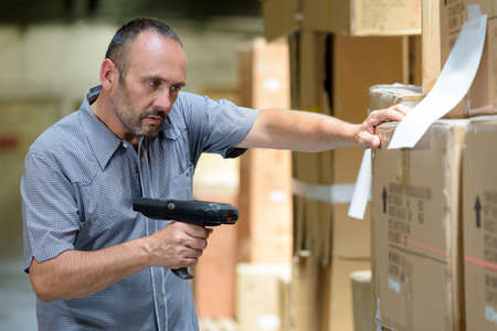 man worker handling barcode scanner in warehouse factory 写真素材