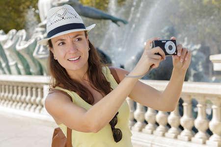 unsure woman taking a photo Imagens