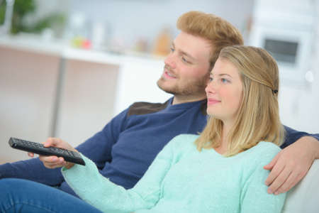 a couple is watching tv