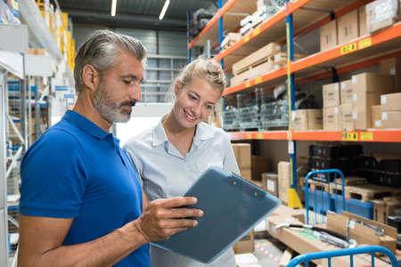 workers in storeroom looking at clipboard