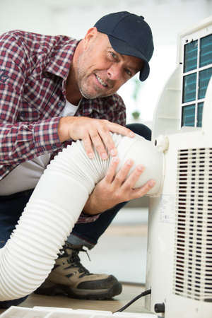 mature male worker carefully installing new ac