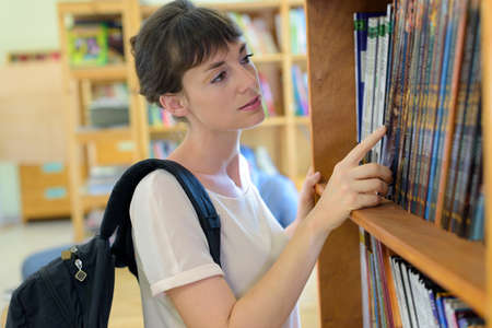 pretty young woman choosing a comic in bookstore
