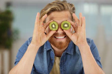 comical image of man covering eyes with kiwi slices