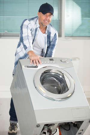 repairman carrying washing machine with hand truck