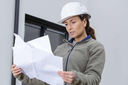 joyful energetic female worker looking at plans
