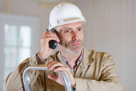 male builder on stepladder using walkie talkie