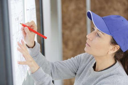 female worker drawing on top of a plan Zdjęcie Seryjne - 134960126