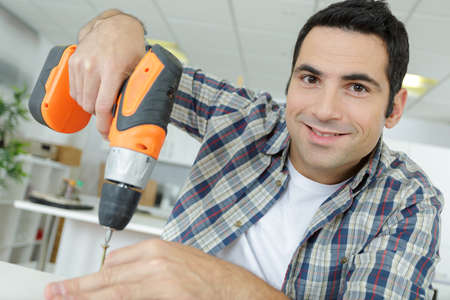happy man holding a cordless drill do it yourself tool Zdjęcie Seryjne - 134960163