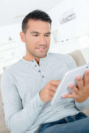 handsome man sat on sofa using digital tablet
