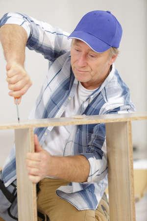 man screwing a screw into wood Zdjęcie Seryjne - 134960198