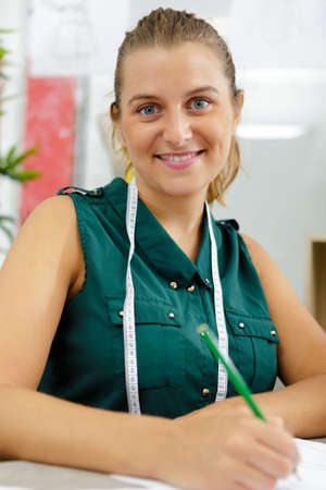 picture of a smiling seamstress holding pencil Zdjęcie Seryjne - 134960242