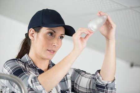 a woman fixing broken lamp