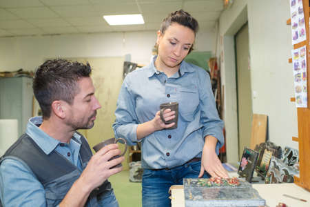 workers having coffee while examining marble commemorative plaque Zdjęcie Seryjne - 134960270