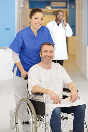 happy nurse talking care of a happy patient in wheelchair Zdjęcie Seryjne - 134960279