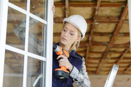 woman unscrews fastening screws handle window Zdjęcie Seryjne - 134960278