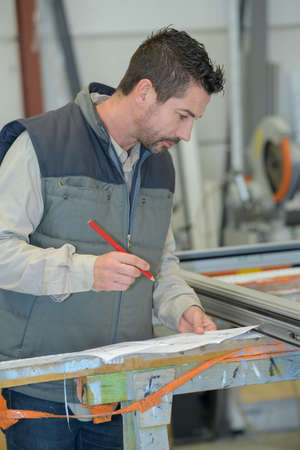 man in factory stood by window framework holding plans Zdjęcie Seryjne - 134960286