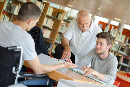 man with student in wheelchair in the library