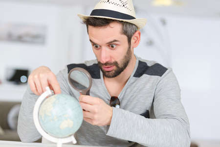 man looking at globe through a magnifying glass