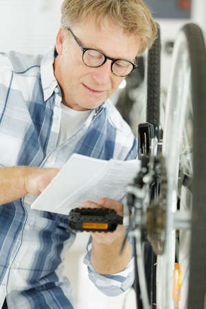 smiling man working on bike Zdjęcie Seryjne - 134960392