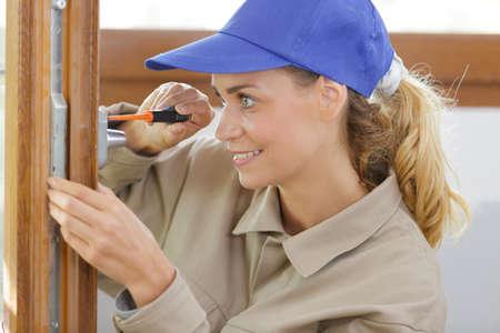 woman fixing door Zdjęcie Seryjne