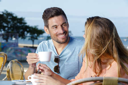 couple drinking coffee in a beach terrace