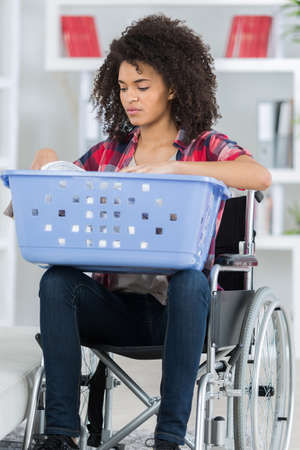 female in wheelchair doing laundry