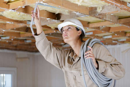 woman installing pipes in the ceiling