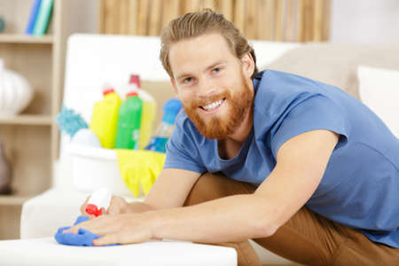 uomo barbuto felice che pulisce il suo appartamento