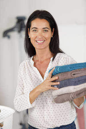 happy woman with stack towels smiling at camera