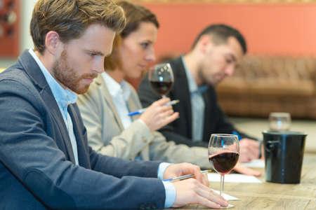 esperti che degustano nuovi tipi di vino a tavola Archivio Fotografico