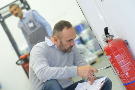 a professional checking fire extinguisher