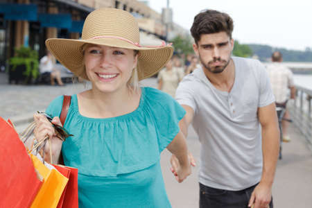 bored man with shopping while with woman