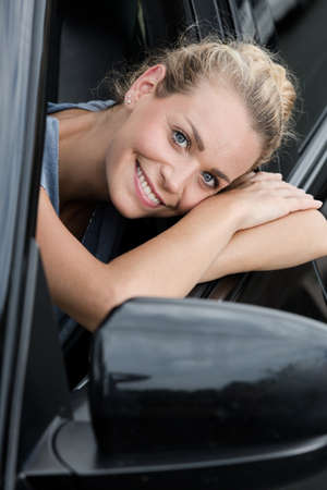 young woman leaning out the car window 写真素材