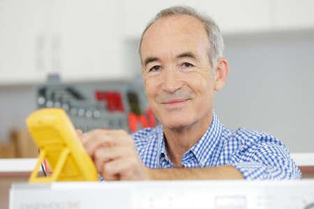 senior man measures the voltage