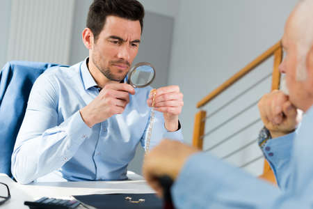 jeweler inspecting ring through magnifying glass in workshop