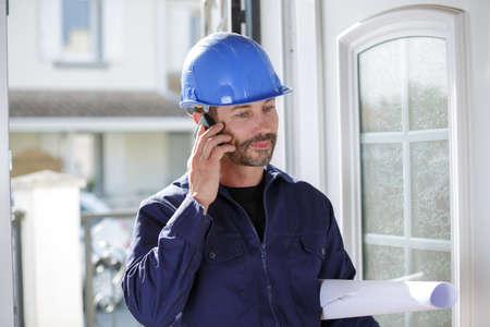 builder wearing protective helmet on the phone