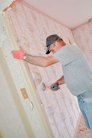 Man working on bedroom wall